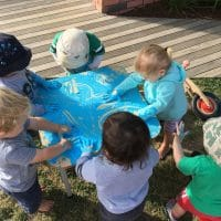 children taking part in messy play which has many learning benefits