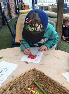child colouring a poppy as part of learning about ANZAC Day